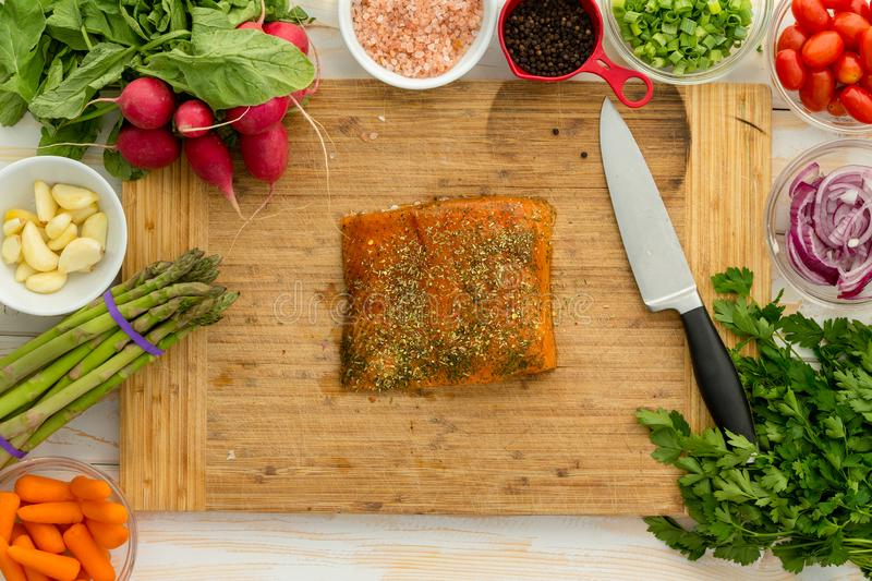 Uncooked fish fillet centered on cutting board stock image