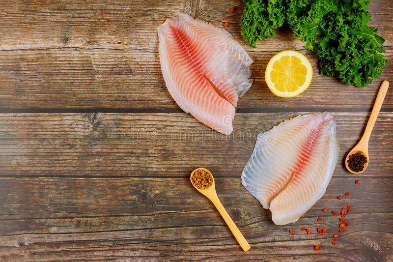 Uncooked fish fillet of tilapia on table with lemon and spices royalty free stock photo