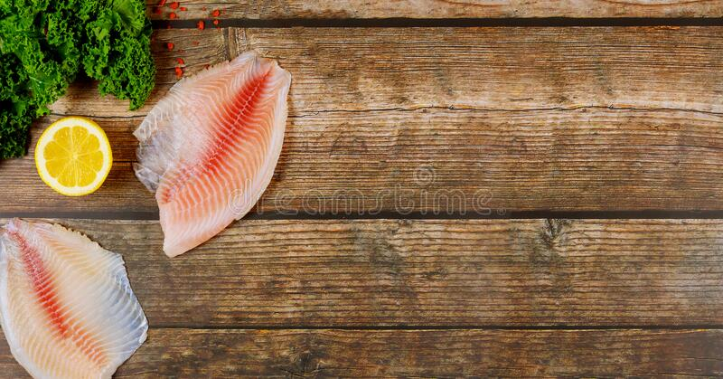 Pink tilapia with lemon and kale on wooden background royalty free stock images