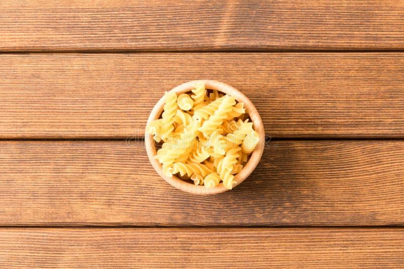 Uncooked fusilli pasta . Wooden background . Italian Food . stock images