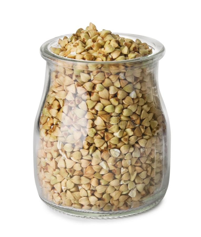 Uncooked green buckwheat grains in jar isolated on white. Uncooked green buckwheat grains in jar isolated stock photography