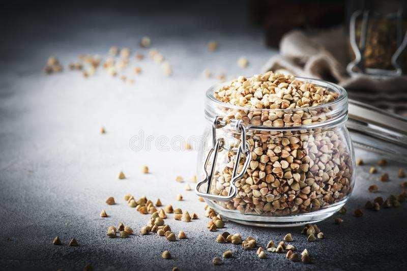 Uncooked green buckwheat groat in glass jar, healthy vegetarian food on gray kitchen table, copy space, selective focus royalty free stock photo