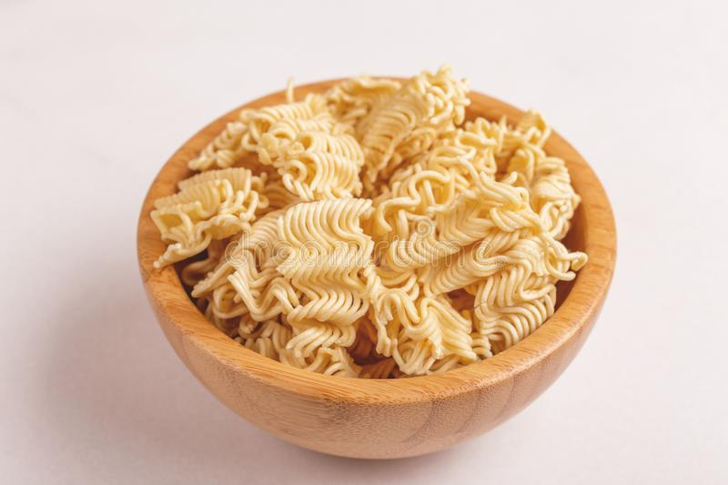 Uncooked instant noodles in wooden bowl on white marble background. Copy space stock photos