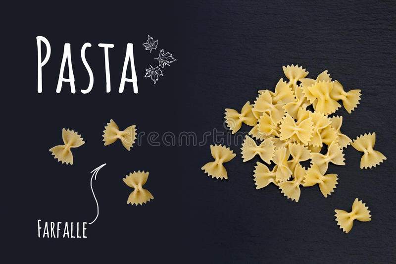 Uncooked Italian pasta Farfalle on black slate stone background. With white lettering, top view royalty free illustration