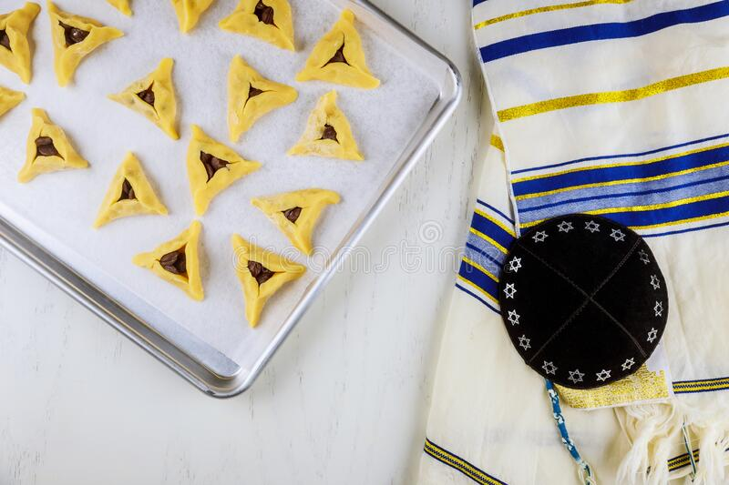 Uncooked jewish cookies on oven tray with kippa and tallit royalty free stock image