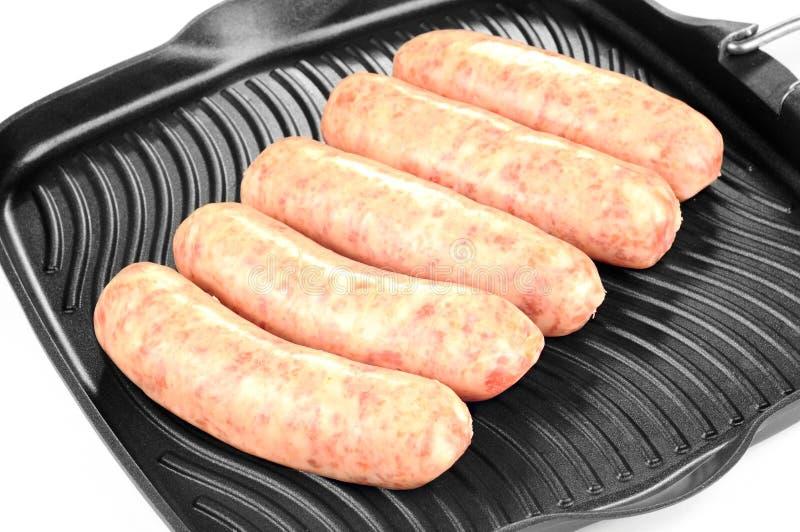 Uncooked kiełbasy na grill niecce, biały tło zdjęcie stock