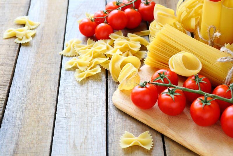 Uncooked makaron i czereśniowych pomidorów gałąź zdjęcie royalty free