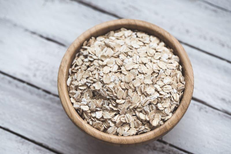 Uncooked oatmeal lub owsa płatki w drewnianym pucharze na białym drewnianym tle zdjęcie royalty free