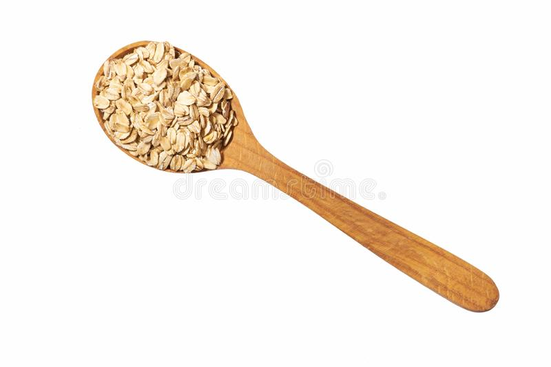 Uncooked oatmeal in wooden spoon isolated on white top view stock photo