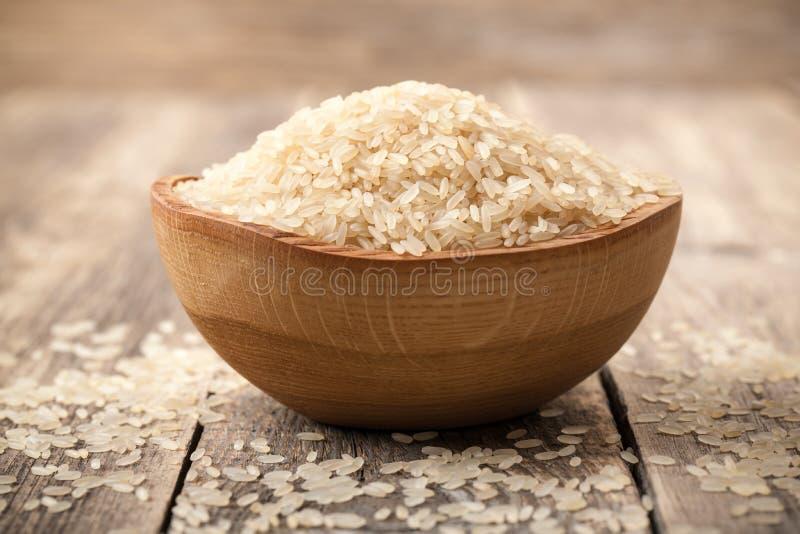 Uncooked obgotowywający ryż w pucharze na drewnianym stole obraz stock