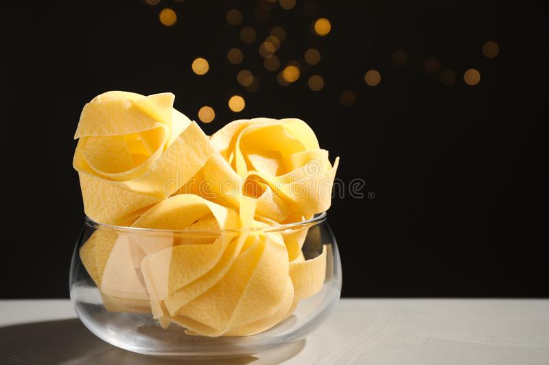 Uncooked pappardelle pasta on grey table against blurred lights royalty free stock photography