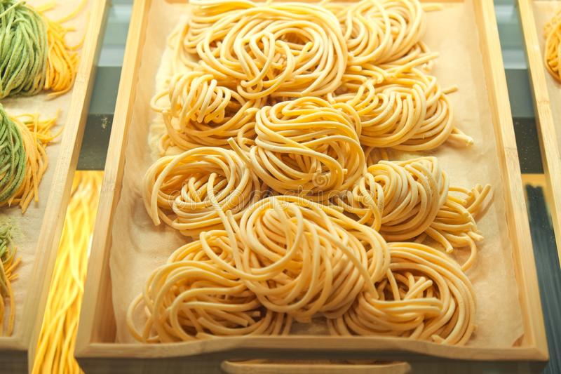 Uncooked pasta closeup in on wooden tray in the shop window. Italian foods concept of spaghetti and menu design.  stock images