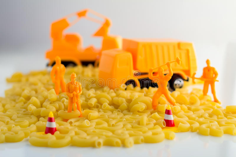 Uncooked pasta and set of workmen on a white background. Food industry concept royalty free stock photography