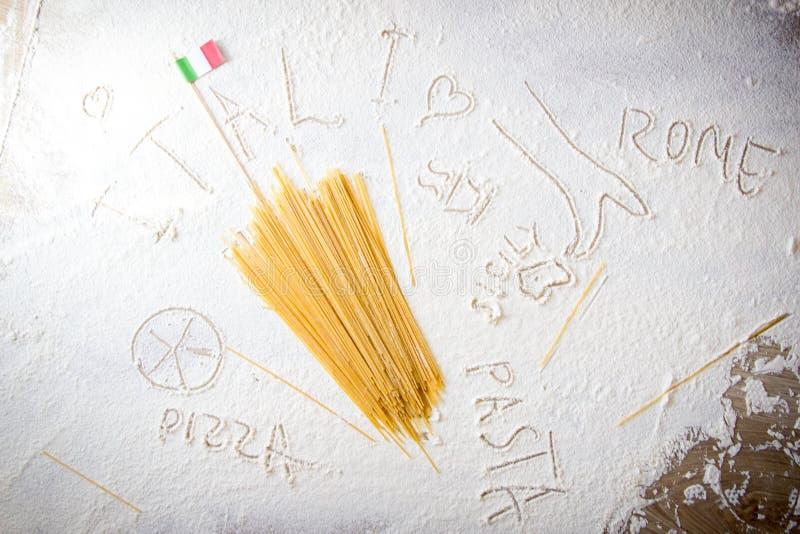 Uncooked pasta spaghetti macaroni and italian flag on floured white background. Food travel italian cuisine concept royalty free stock photo