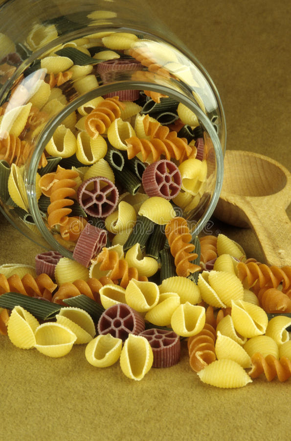 Uncooked pasta spills from glass jar royalty free stock photo
