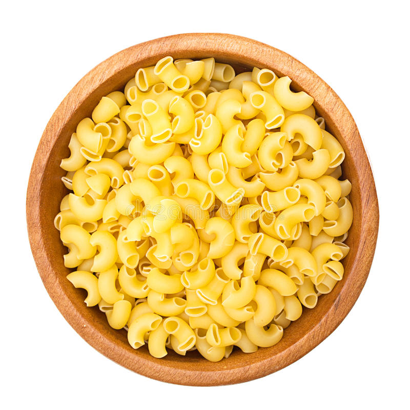 Uncooked pasta in a wooden bowl stock image