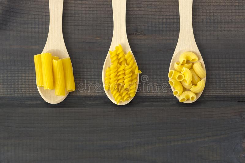 Uncooked pasta in a wooden spoon stock photography