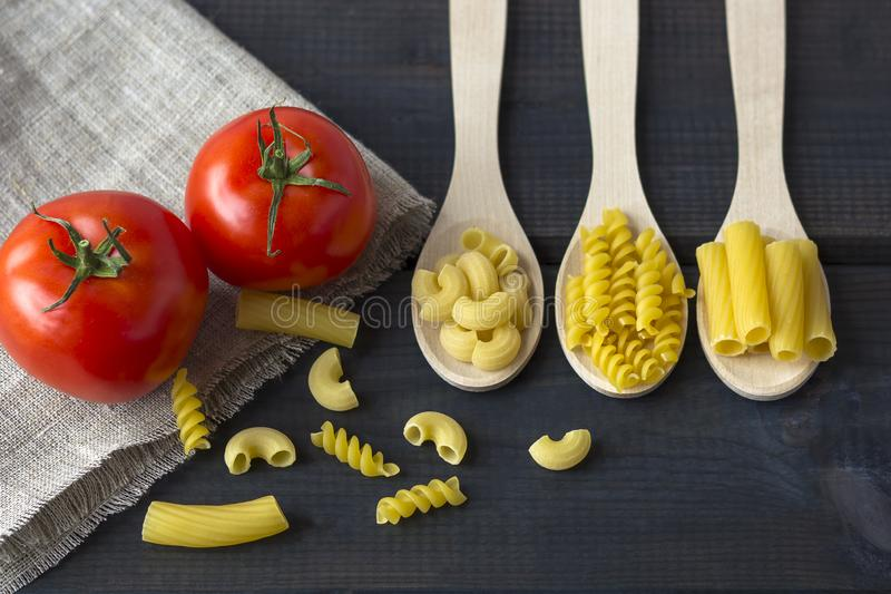 Uncooked pasta in a wooden spoon royalty free stock photography