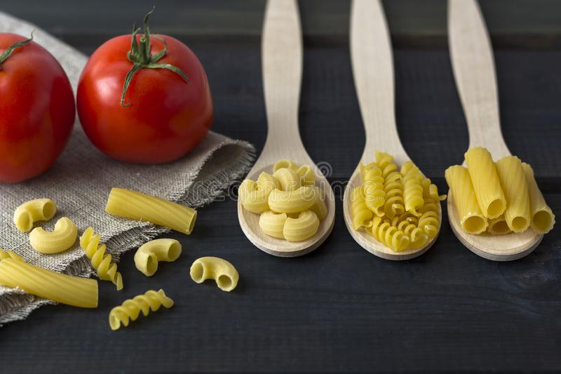 Uncooked pasta in a wooden spoon royalty free stock images
