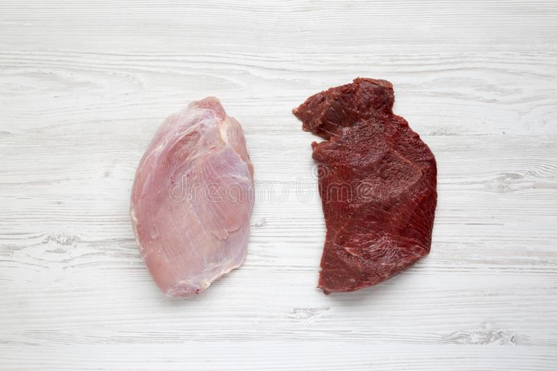 Uncooked raw beef meat and turkey breast on white wooden background, top view. Flat lay. stock photos