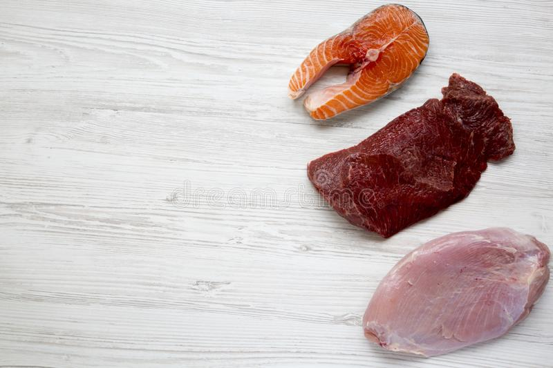 Uncooked raw salmon steak, beef meat and turkey breast on white wooden background, top view. Flat lay. stock photo