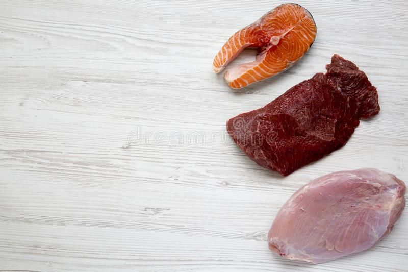 Uncooked raw salmon steak, beef meat and turkey breast on white wooden background, top view. Flat lay. From above. stock photo
