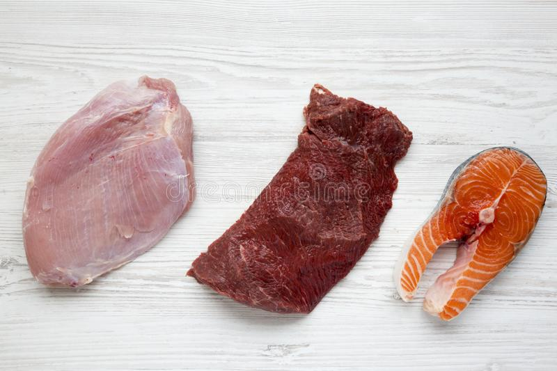 Uncooked raw salmon steak, beef meat and turkey breast on white wooden background, top view. Flat lay royalty free stock photos