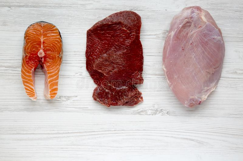 Uncooked raw salmon steak, beef meat and turkey breast on white wooden background, top view. Flat lay. royalty free stock photo