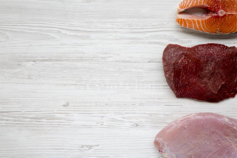 Uncooked raw salmon steak, beef meat and turkey breast on white wooden background, top view. Flat lay. royalty free stock photos