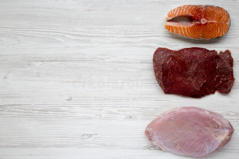 Uncooked raw salmon steak, beef meat and turkey breast on white wooden background, top view. Flat lay. stock images