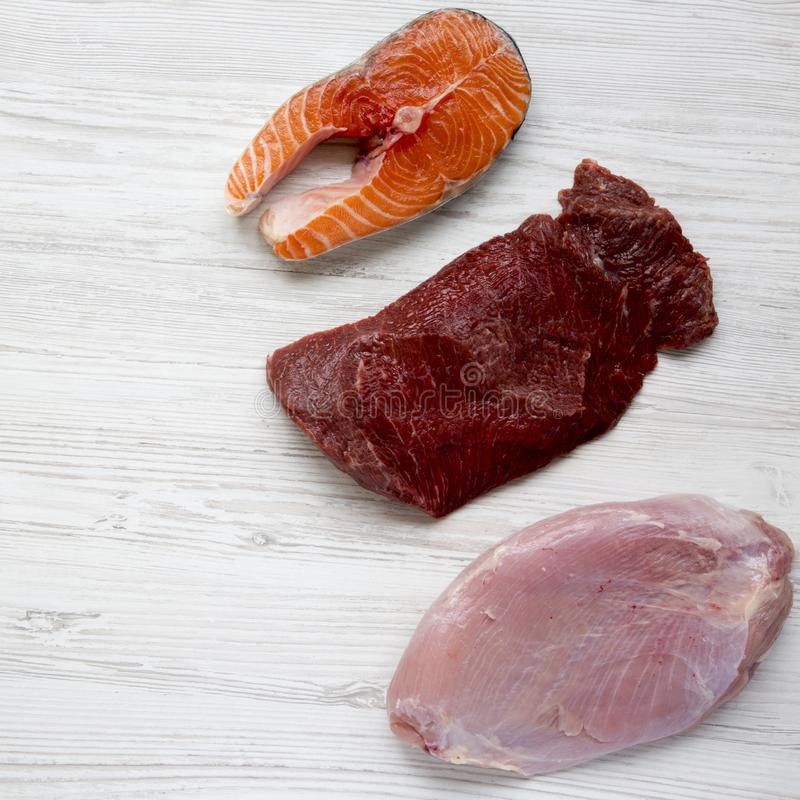 Uncooked raw salmon steak, beef meat and turkey breast on white wooden table, overhead view. Flat lay. From above. royalty free stock photo
