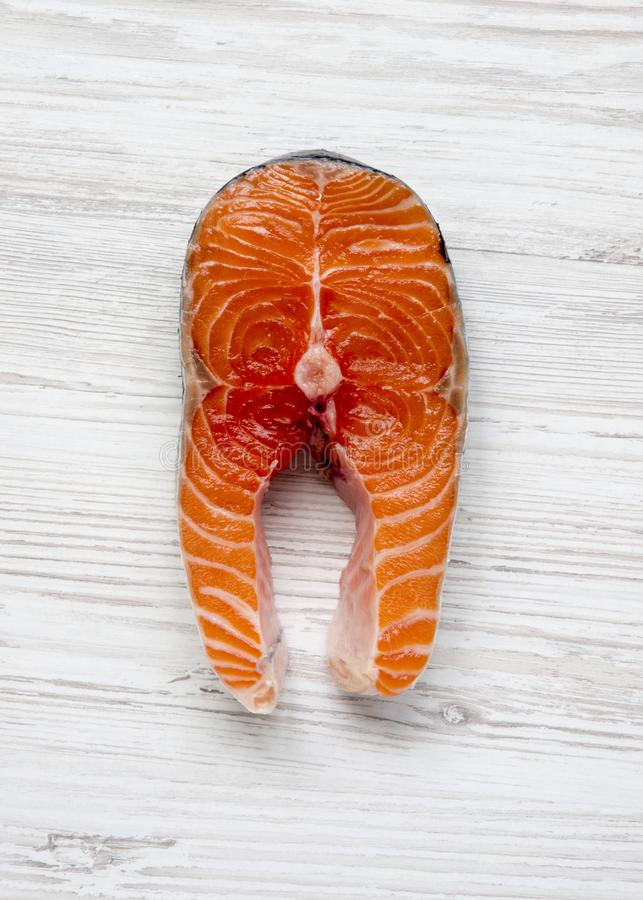 Uncooked raw salmon steak on a white wooden table, top view. Flat lay. From above, overhead royalty free stock image