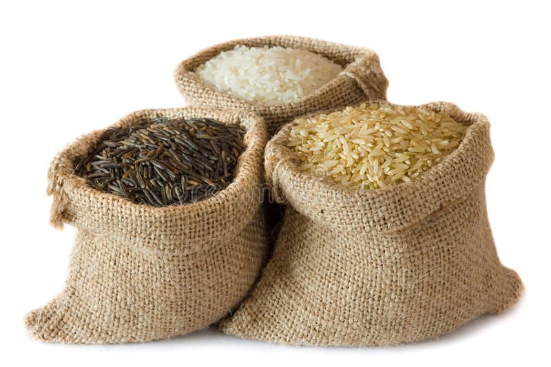 Uncooked rice in small burlap sacks stock photos