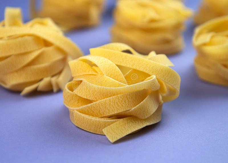 Uncooked rolled traditional italian pasta on violet background. Portion of raw fettuccine or tagliatelle or pappardelle. royalty free stock image