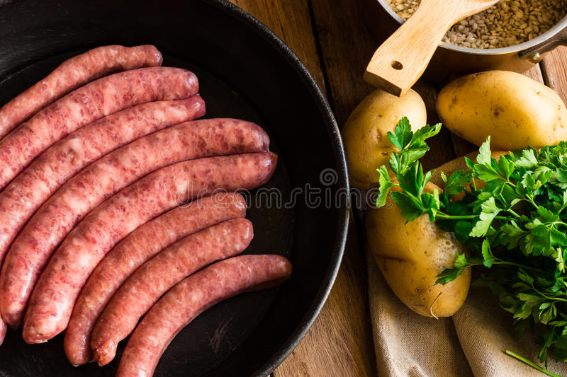 Uncooked sausages in iron cast pan, potatoes and fresh parsley, pot with rice, top view royalty free stock photos