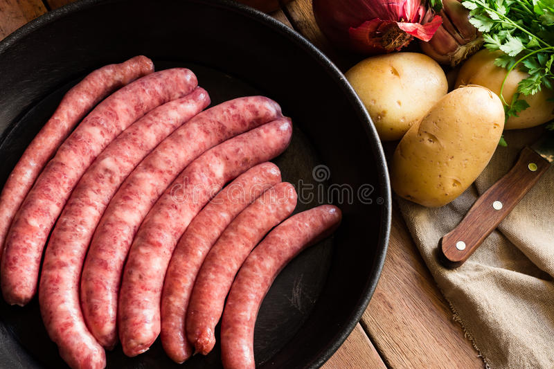 Uncooked sausages in iron cast pan, vegetables on table, knife, linen towel, dinner preparation royalty free stock images