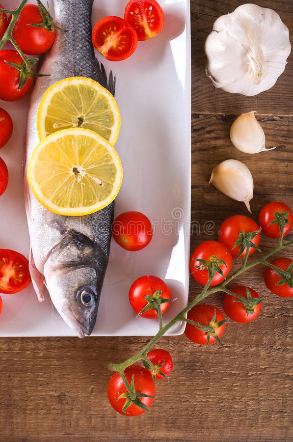 Uncooked sea bass. Image of uncooked sea bass on white dish royalty free stock photography