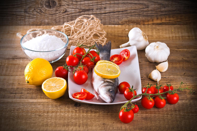 Uncooked sea bass. Image of uncooked sea bass on white dish royalty free stock photos