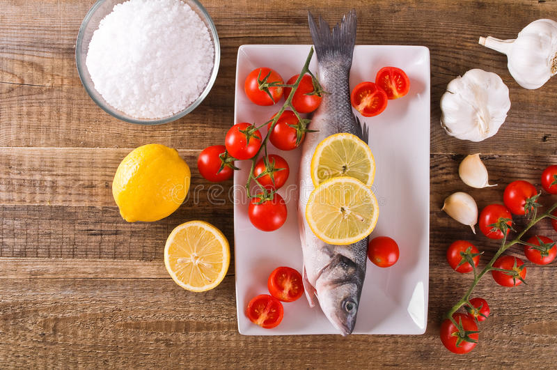 Uncooked sea bass. Image of uncooked sea bass on white dish royalty free stock image