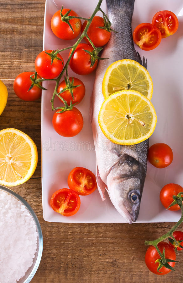 Uncooked sea bass. Image of uncooked sea bass on white dish stock photos