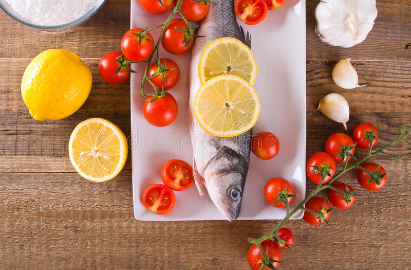 Uncooked sea bass. Image of uncooked sea bass on white dish stock photo