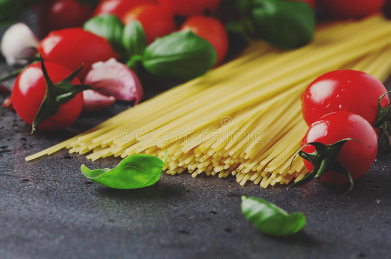 Uncooked spaghetti with tomato and basil stock images
