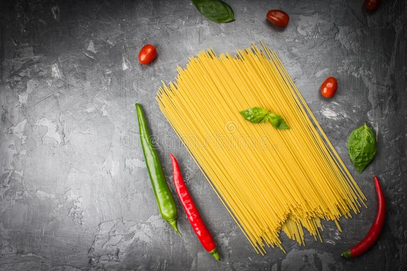 Uncooked spaghetti with tomatoes, pepper and basil on a gray bac stock image