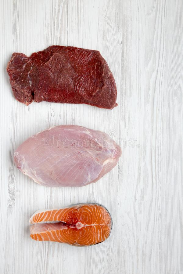 Uncooked surowy wołowiny mięso, indycza pierś i łososiowy stek na białym drewnianym tle, odgórny widok Mieszkanie nieatutowy obraz stock