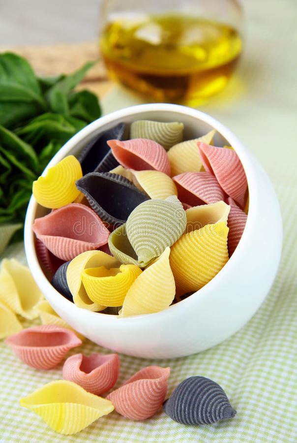 Uncooked tricolor pasta in bowl royalty free stock photo