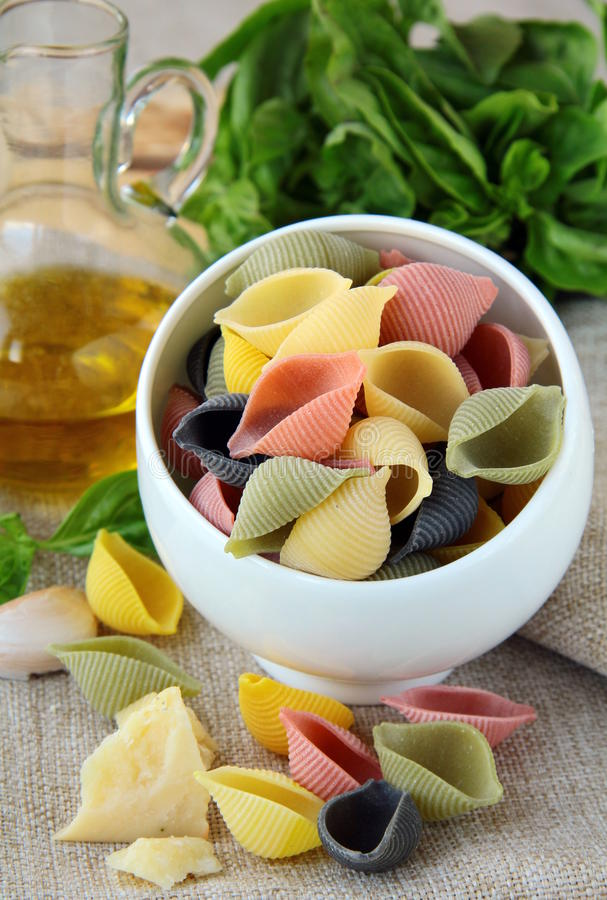 Uncooked tricolor pasta in cup royalty free stock photos