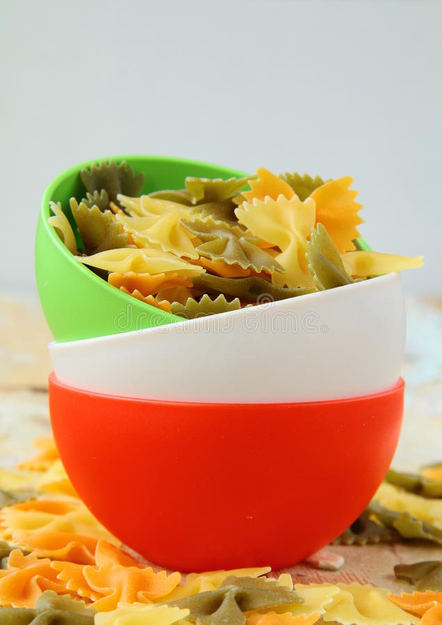 Uncooked tricolor pasta in cups stock photos