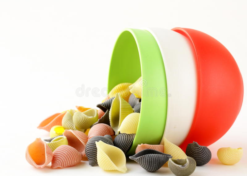 Uncooked tricolor pasta in cups royalty free stock image