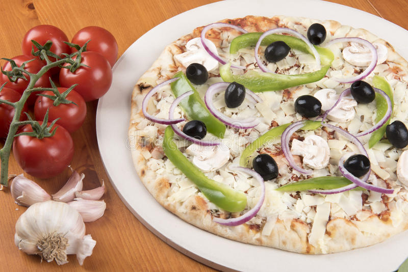 Uncooked vegetarian pizza with olives, peppers, onion, mushrooms and garlic stock photo