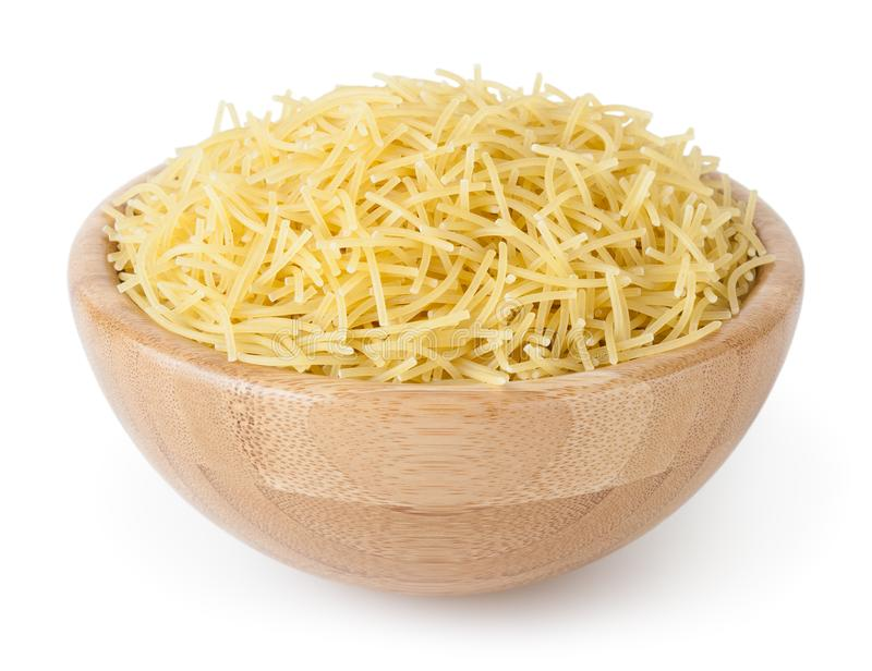 Uncooked vermicelli pasta in wooden bowl isolated on white. Background with clipping path stock photo